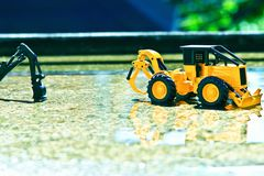 Dwa folklene zabawki na nieznacznie mokrej cementowej podłoga w wiosna deszczu nieznacznie błyszczą w wodzie Zdjęcie Stock