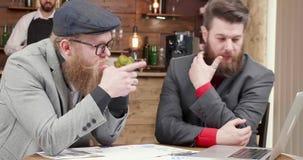 Dwa freelancers patrzeje laptopu ekran i porównuje dane zbiory wideo