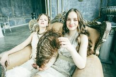 Dwa fryzury ?adna bli?niacza siostrzana blond k?dzierzawa dziewczyna w luksusu domu wn?trzu wp?lnie, bogaci m?odzi ludzie poj?? fotografia stock