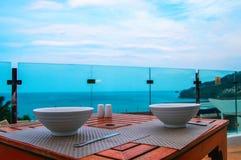Dwa głębokiego zupnego talerza biały ceramiczny stojak na drewnianym stole w na otwartym powietrzu restauraci na tle morze obraz stock
