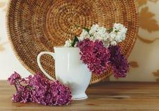 Dwa gałąź Biały i Purpurowy bez w Ceramicznej filiżance Rottan talerz Drewniany tło, Zdjęcia Royalty Free