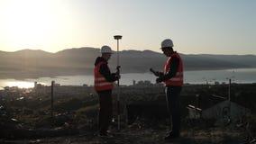 Dwa geodeta wykonuje geodesic pomiary na górze góry w hełmach zdjęcie wideo