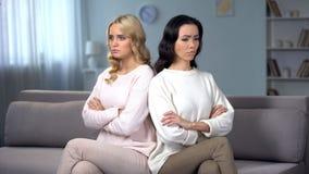 Dwa gniewnej kobiety jest w be?ta obsiadaniu na kanapie, konflikt mi?dzy przyjaci??mi zdjęcie stock