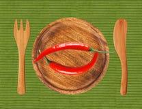 Dwa gorącego chili pieprzu na drewnianym talerzu nad zielonym płótnem Obraz Royalty Free