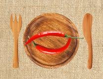 Dwa gorącego chili pieprzu na drewnianym talerzu nad burlap Obrazy Royalty Free