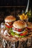 Dwa hamburgeru na drewno stole Zdjęcia Royalty Free