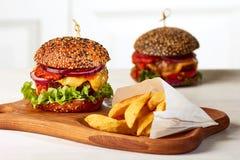 Dwa hamburgeru z francuskimi dłoniakami Zdjęcie Stock