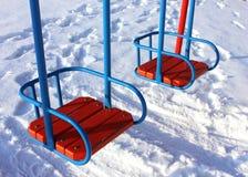Dwa huśtawki na playgound w zimie Zdjęcia Royalty Free