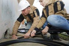 Dwa hydraulika załatwia kanalizaci drymbę przy budową fotografia royalty free
