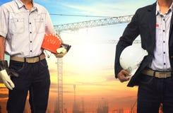 Dwa inżynierów mężczyzna pracuje z białym zbawczym hełmem przeciw żurawiowi Zdjęcia Royalty Free
