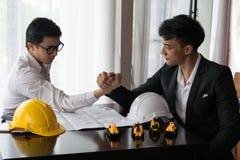 Dwa inżynier lub biznesmen angażują w ręki zapaśnictwie Zdjęcie Stock