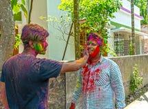 Dwa indianina brat barwi each inny podczas Holi festiwalu w India zdjęcie royalty free