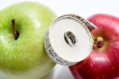 Dwa jabłka i pomiarowej taśma na korkują powierzchnię Fotografia Royalty Free