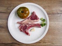 Dwa jagnięcego kotlecika z pomidorem i czosnkiem w talerzu Fotografia Stock