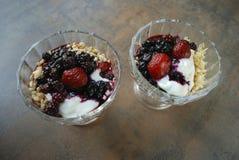 Dwa jagoda deseru z jogurtu i ryż płatkami w szklanej filiżance Obraz Royalty Free