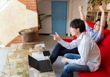 Dwa Japońskiego mężczyzna ogląda sporty gemowych w pokoju mieszkanie Obrazy Stock