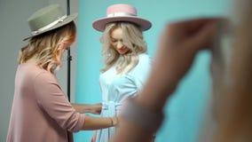 Dwa jednakowej dziewczyny w kapeluszach i sukniach fotografują w studiu zbiory