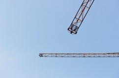 dwa jib żurawia przeciw bezchmurnemu niebieskiemu niebu Zdjęcie Stock