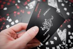 _ Dwa joker karty w ręce nad czarny barwiony karta do gry tło obraz royalty free