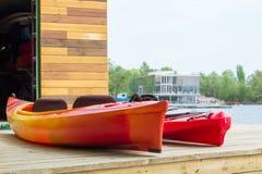 Dwa kajak łodzi na drewnianym pokładzie przy stacyjną pobliską rzeką Zdjęcie Royalty Free