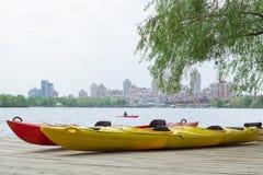 Dwa kajak łodzi na drewnianym pokładzie przy stacyjnym pobliskim jeziorem Zdjęcie Royalty Free