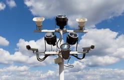 Dwa kamery bezpieczeństwa, floodlights i głośnika przeciw niebieskiemu niebu, Obrazy Stock