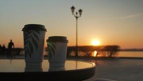 Dwa kartonowej filiżanki z kawą stoją w stole quay kawiarnia w zmierzchu, sylwetka ludzie zbiory