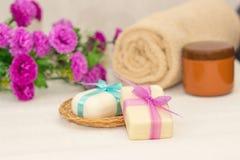 Dwa kawałka mydło z koszem z łęki, kwiaty, ręcznik a Fotografia Royalty Free