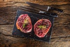 Dwa kawałka surowego wołowina giczoła na łupek desce i drewnianym stole Obrazy Stock