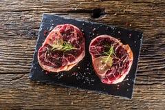 Dwa kawałka surowego wołowina giczoła na łupek desce i drewnianym stole Zdjęcia Stock