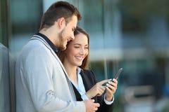 Dwa kierownictwa używa telefon komórkowego na ulicie obraz royalty free