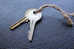 Dwa klucza wiążącego z sznurkiem na czarny skórze Obrazy Royalty Free