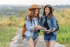 Dwa kobiet gmerania kierunek na lokacji mapie podczas gdy podróżujący zdjęcie royalty free