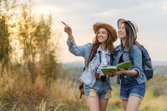 Dwa kobiet gmerania kierunek na lokacji mapie podczas gdy podróżujący zdjęcie stock