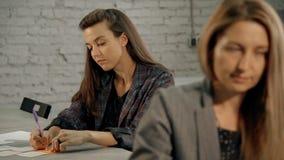 Dwa kobiet obsiadanie za pracy biurkiem w biurze zbiory