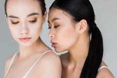 dwa kobiet wielokulturowy pozować odizolowywam na szarość fotografia stock