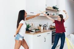 Dwa kobiet wizerunek że walczą na kordzikach drewnianymi szpachelkami w kuchni Zdjęcia Stock