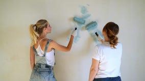 Dwa kobieta pracownika używa rolownika malować ściany w domu lub mieszkaniu Budowa, naprawa i odświeżanie, zbiory