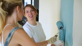 Dwa kobieta pracownika używa rolownika malować ściany w domu lub mieszkaniu Budowa, naprawa i odświeżanie, zdjęcie wideo