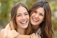 Dwa kobieta przyjaciela śmia się z perfect białych zęby