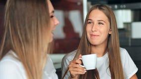 Dwa kobieta przyjaciela w kuchennej pije kawie, opowiadający zabawę i mieć zdjęcie wideo