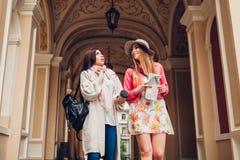 Dwa kobieta turysty opowiada podczas gdy iść zwiedzać w Odessa Szczęśliwi przyjaciół podróżnicy używa mapę i pijący kawę fotografia stock