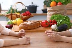 Dwa kobiety dyskutuje nowego menu w kuchni, zamykają up Ludzkie ręki dwa persons gestykuluje przy stołem wśród Zdjęcia Royalty Free