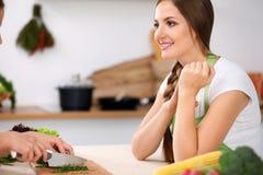 Dwa kobiety gotują w kuchni Przyjaciele ma przyjemności rozmowę podczas gdy przygotowywający sałatki i kosztujący Przyjaciela sze Obrazy Stock