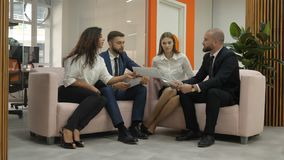 Dwa kobiety i dwa mężczyzna siedzą na devanchiki w biurze i jeden mężczyzna wyjaśnia esencję dokumenty zbiory wideo