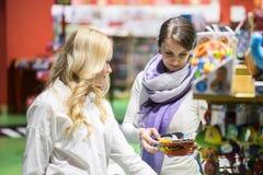 Dwa kobiety jak homoseksualna para lub przyjaciele wybierają zabawkarskiego zabawę w dużym kolorowym supermarkecie i dostawać zdjęcie stock