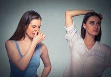 Dwa kobiety, jeden szczypa nos coś śmierdzą underarm, dziewczyny fotografia royalty free