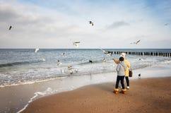 Dwa kobiety karmią ptaki przy plażą na zimnym dniu Obrazy Stock