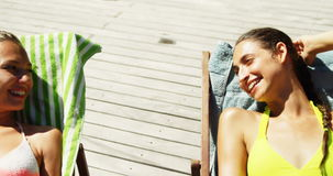 Dwa kobiety oddziała wzajemnie z each inny podczas gdy sunbathing blisko pływackiego basenu zdjęcie wideo