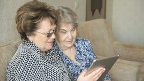 Dwa kobiety ogląda obrazki na cyfrowej pastylce zbiory